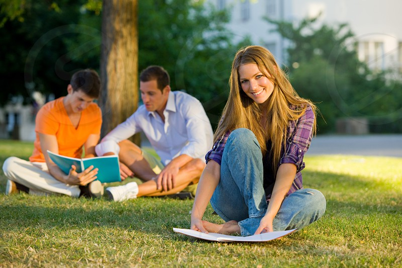People; Casual Clothing; Friendship; Beginnings; Support; Discussion; Education; Horizontal; Full Length; Outdoors; 20-24 Years; Book; Cheerful; Caucasian Ethnicity; Multi-Ethnic Group; Pen; Sitting; Reading; Smiling; Holding; Studying; University; Campus; Day; Face To Face; Learning; Adult; Young Adult; Color Image; Grass; Three People; Young Men; Young Women; Building Exterior; Photography; University Student; Student; Male with Group of Females; Adults Only; Relaxation; Preparation photo
