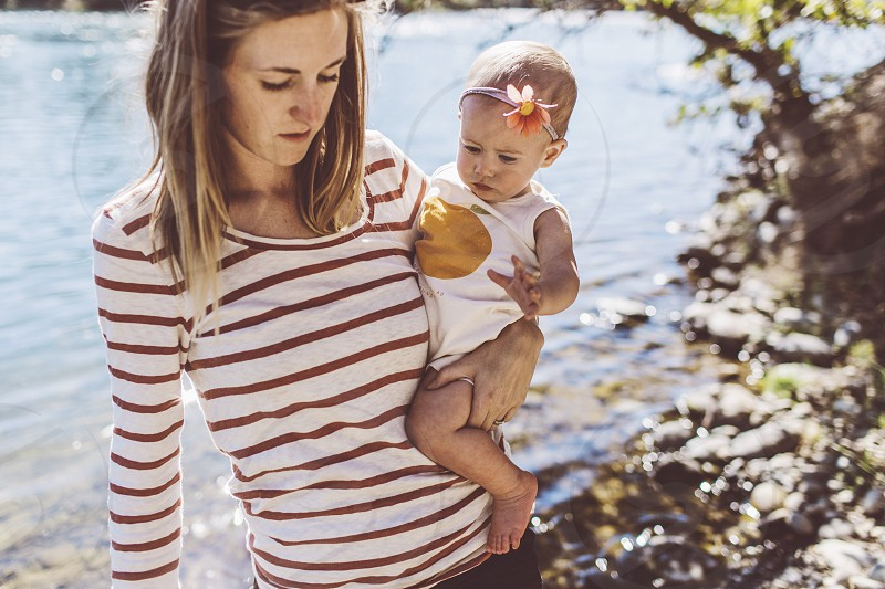 woman wearing white and brown stripe long sleeve shirt carrying her baby besides body of water photo