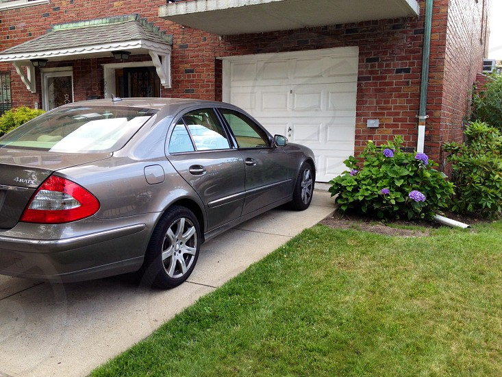 gray sedan parked in front of garage photo