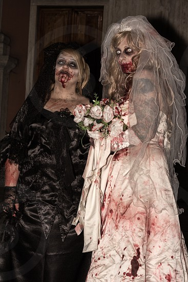 woman zombie in black mourning dress and bride zombie woman photo