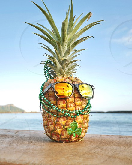 St Patrick's day in Hawaii be like sunglasses pineapple and shamrock green beads at the ocean photo