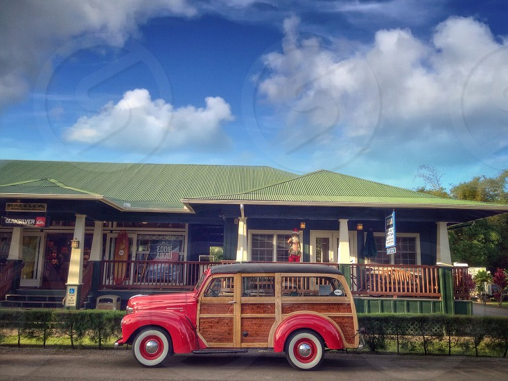 Red and wood vintage woody car in front of the green craftsman home photo