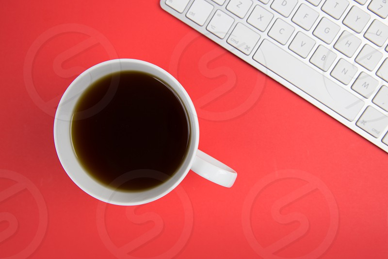Coffee cup and computer keyboard on red background photo