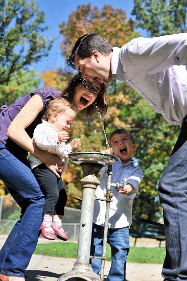shallow focus photography man drinking on water fountain beside woman with children showing smile during daytime photo