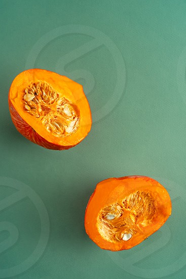 Two pumpkin halves with seeds on green background. Top view vertical orientation with copy space photo