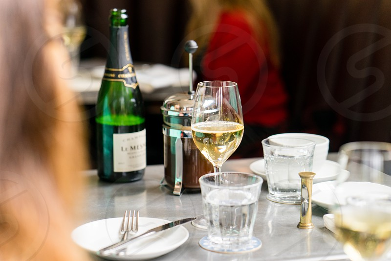 a cup of champagne beside stainless fork and knife photo