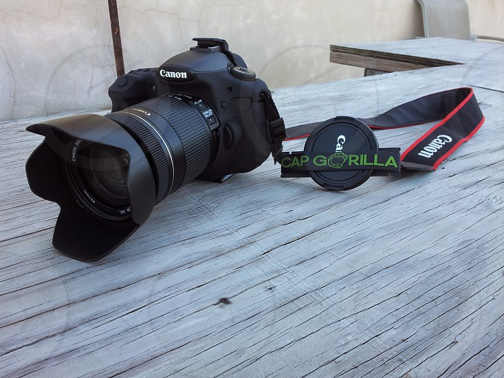 black Canon DSLR camera on top of brown wooden furniture photo