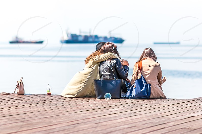 Girls Friends Taking Selfie And Using Mobile Phones At The Dock photo