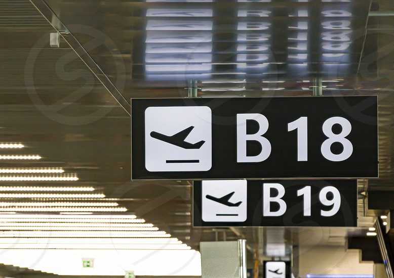 Information panel with the pictogram of an airplane taking off to indicate the boarding gate B 18 inside an airport. Concept of travel and mode of transport photo