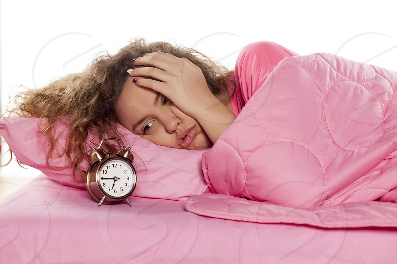 nervous young woman wakes up with an alarm clock photo