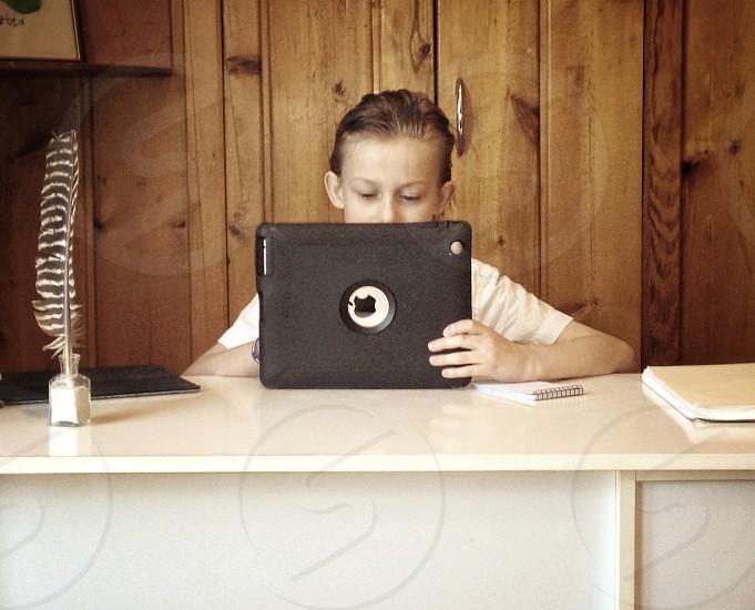 boy using white ipad photo