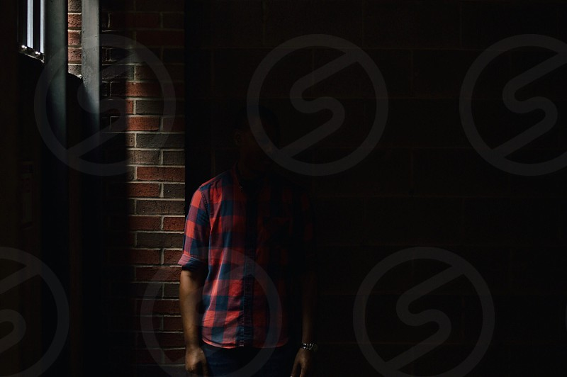 man wearing a red and black checked button up shirt standing against a brick wall in shadows photo