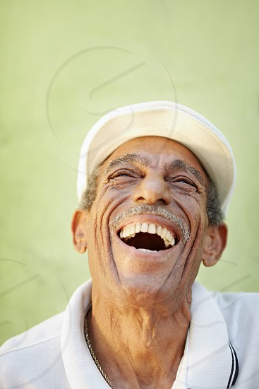 60s; 70s; aged; camera; cheerful; confident; copy space; delighted; elderly; enjoy; enjoyment; euphoria; front view; glad; good news; grandfather; green; happiness; happy; hat; head and shoulders; health; healthy; hispanic; joy; latin; laughing; lifestyle; looking; looking up; male; man; natural; old; older; one; one person; optimistic; outdoors; people; person; portrait; positive; retired; retirement; satisfaction; senior; smiling; wall; white photo