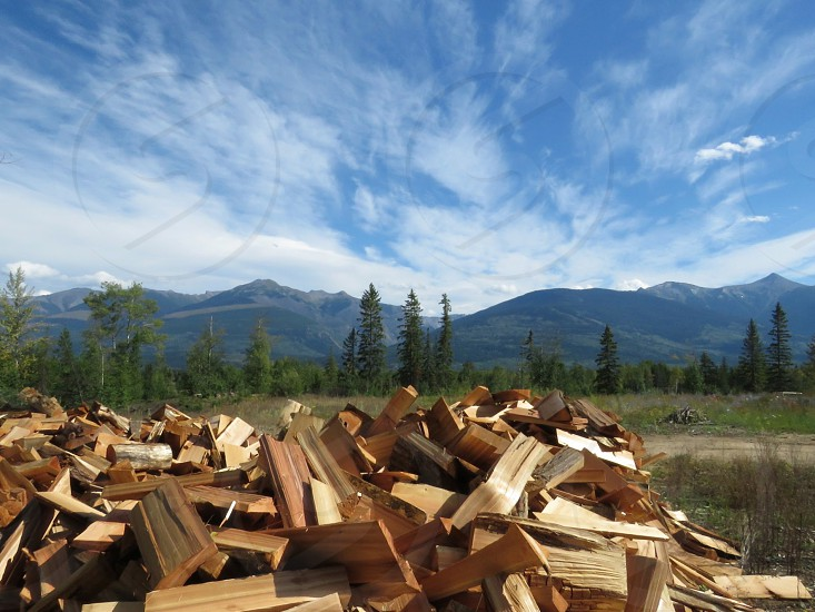 household chores chopping wood wood pile mountains trees field blue sky wispy clouds exercise nature alternate heat energy work homestead summer breathtaking view photo
