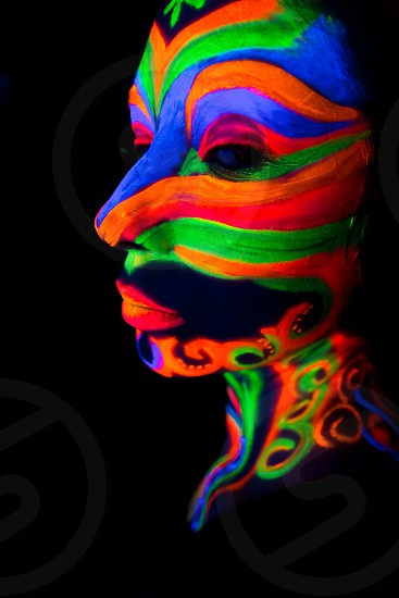 Woman with make up art of glowing UV fluorescent powder. photo