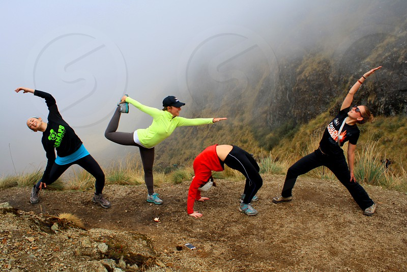 4 people doing different stance on hill with white clouds behind photo