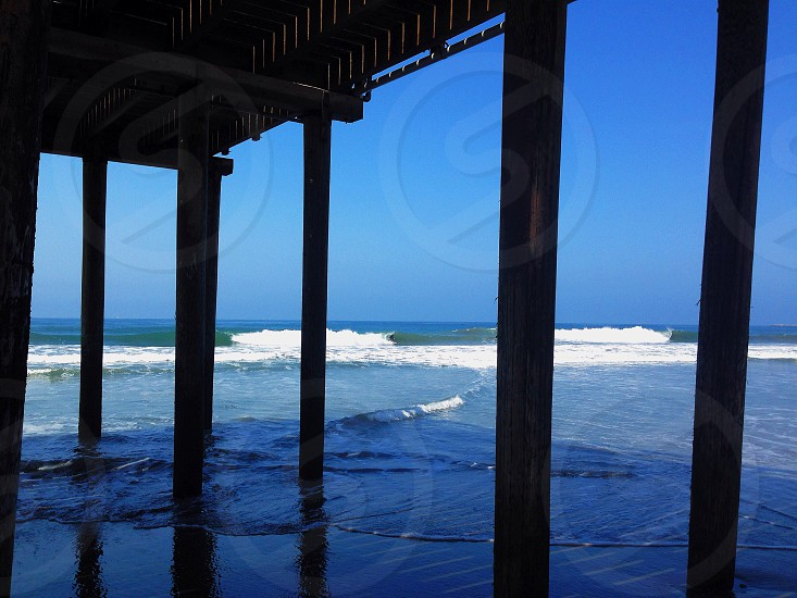 black wooden pier by the beach  photo