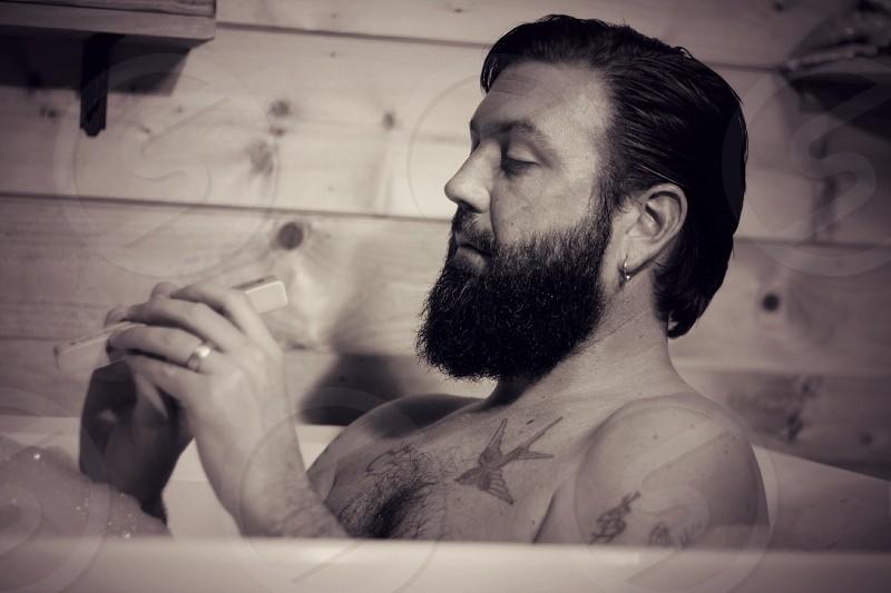man holding remote on bath tub photo
