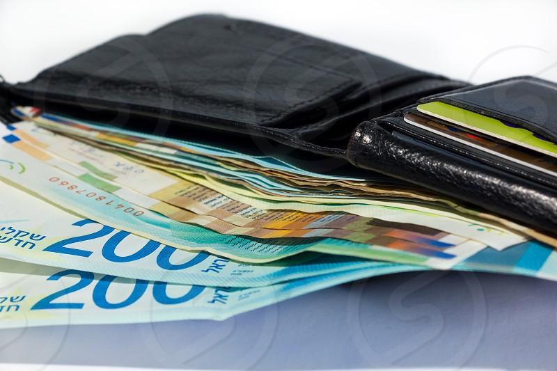 Stack of various of israeli shekel money bills in open black leather wallet. photo