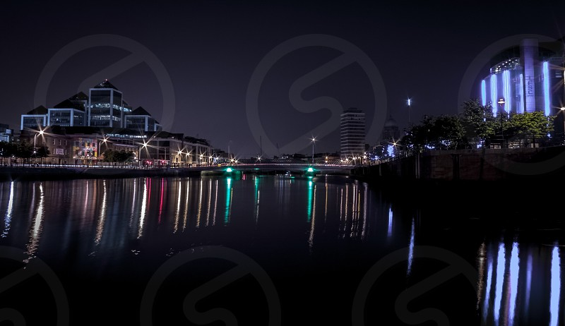 Dublin Ireland city town buildings street architecture bridge river Liffey reflection night skyline cityscape. photo