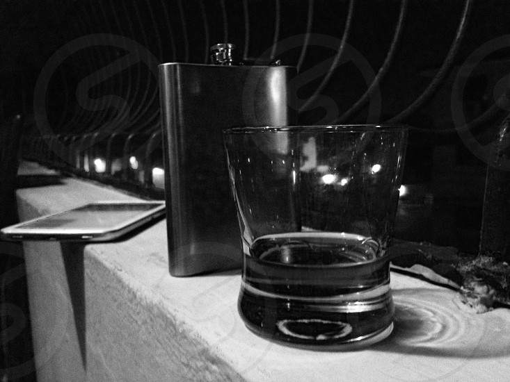 grayscale photography of hip flask beside shot glass photo