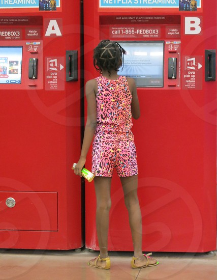 Girl choosing movie at A and B kiosks photo
