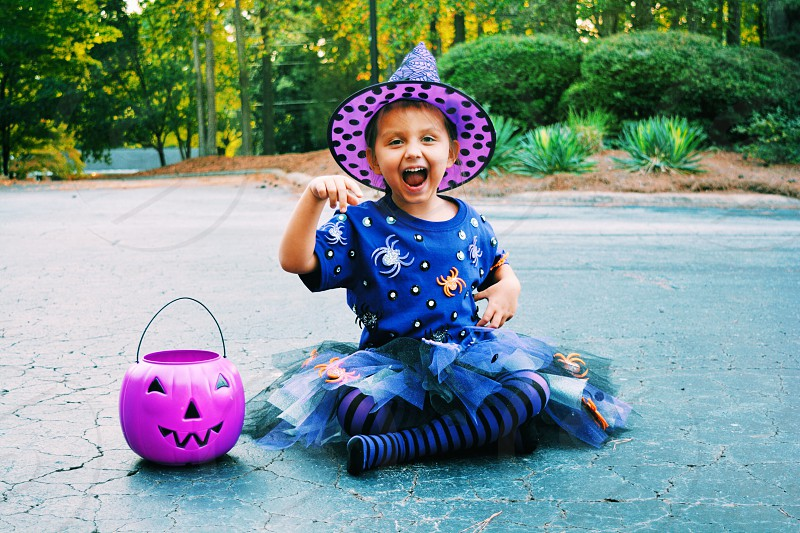 girl in blue witch costume sitting on ground photo