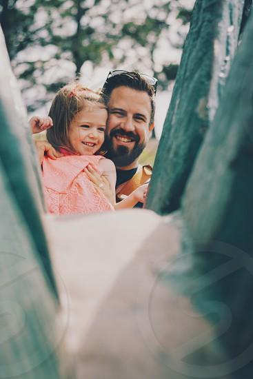 man beside girl in orange shirt smiling photo