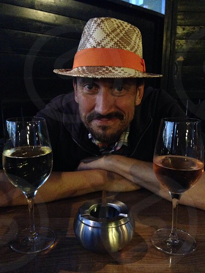 man in plaid panama hat smiling in between wine glass photo