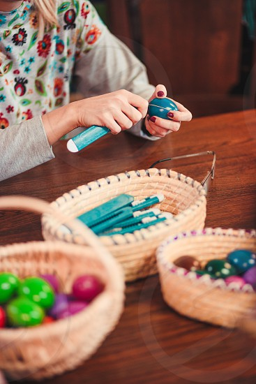 Woman decorating the Easter eggs by scratching patterns on dyed eggs. Traditional Easter time spring time new beginnings. Candid people real moments authentic situations photo