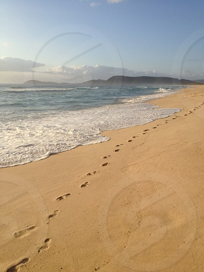 Beach sand footprints waves Australia photo