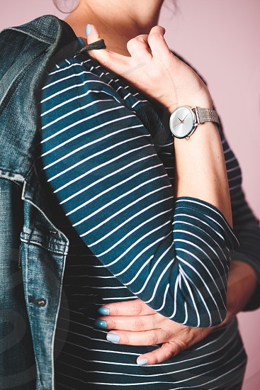 Woman wearing silver wristwatch and blue blouse in white stripes holding jeans jacket. Standing in front of pastel pink wall photo