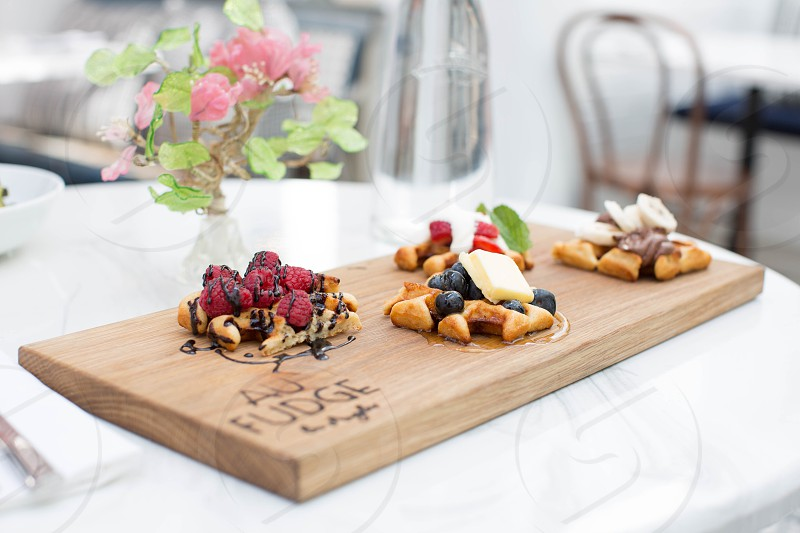 bread with raspberry and blueberry toppings on brown wooden board photo