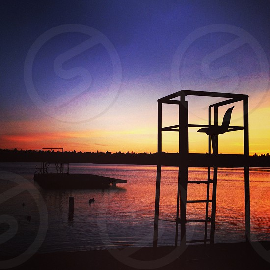 life guard seat neck to lake with diving dock at sunset photo