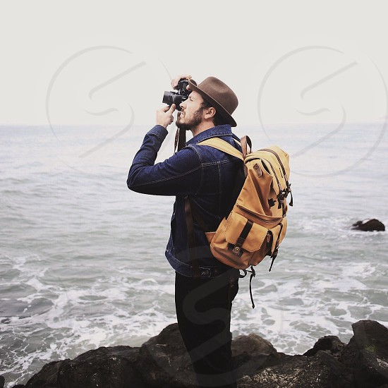 man with beard wearing a brown hat and tan backpack standing on a cliffside over water taking a photo photo
