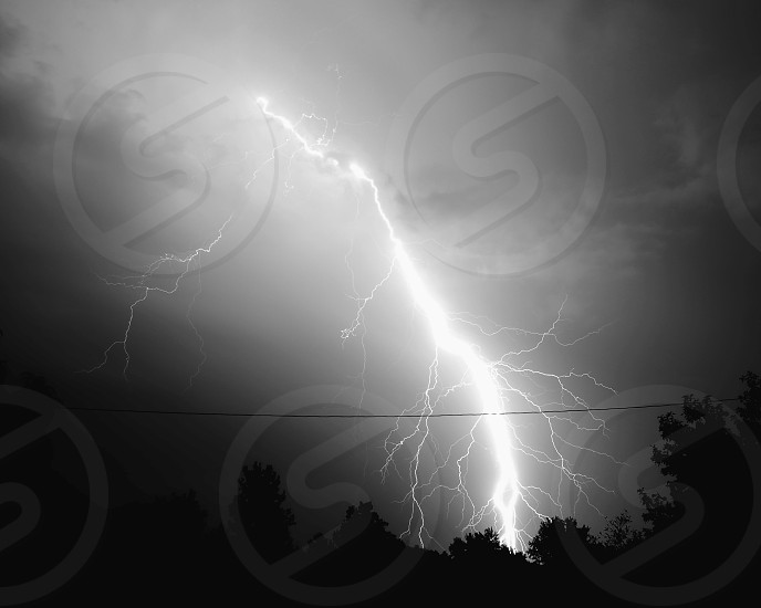 lightning striking surface of the earth in gray scale photo