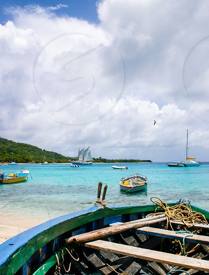 Row boat and sail boats. Mustique Harbor Caribbean Sea. photo