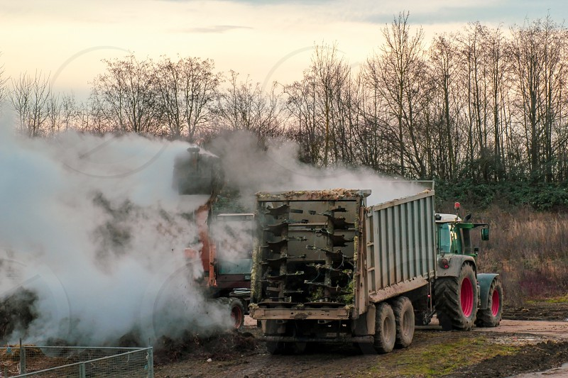 Excavator loads manure hovering in the cold air into a tractor with a trailer. Late fall. Animal husbandry and farming concept. photo