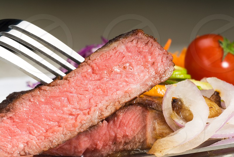 fresh juicy beef ribeye steak sliced with lemon and orange peel on top  and vegetable beside photo