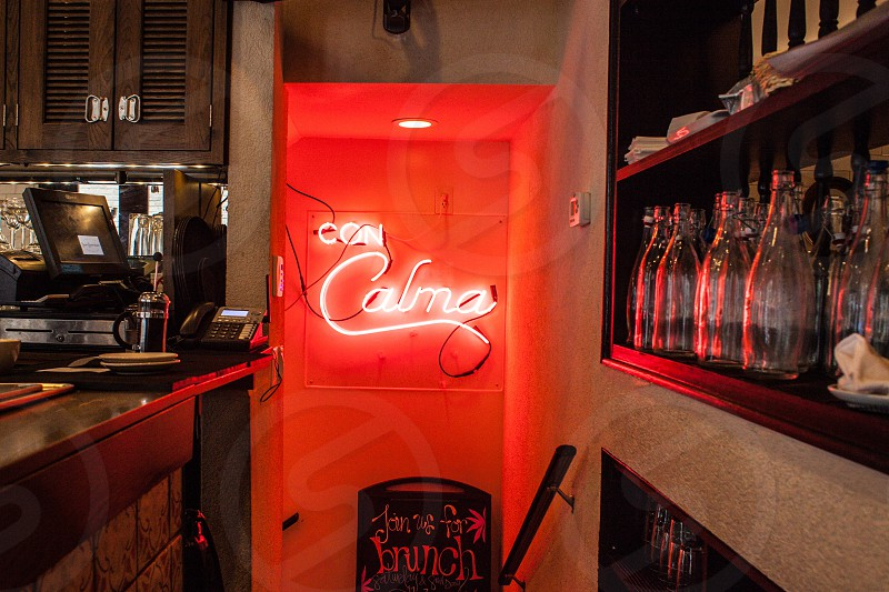 con calma neon signage with mini bar view facing the piled glass bottle photo