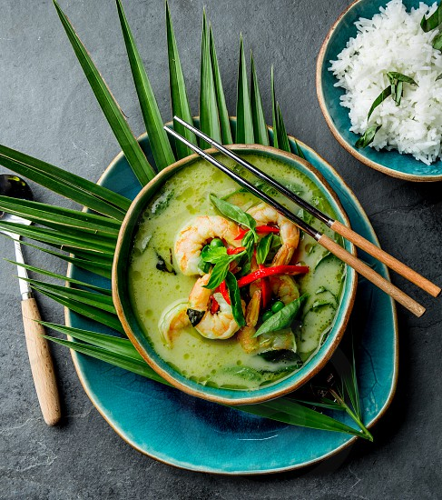 THAI SHRIMPS GREEN CURRY. Thailand tradition green curry soup with shrimps prawns and coconut milk. Green Curry in blue plate on gray background photo