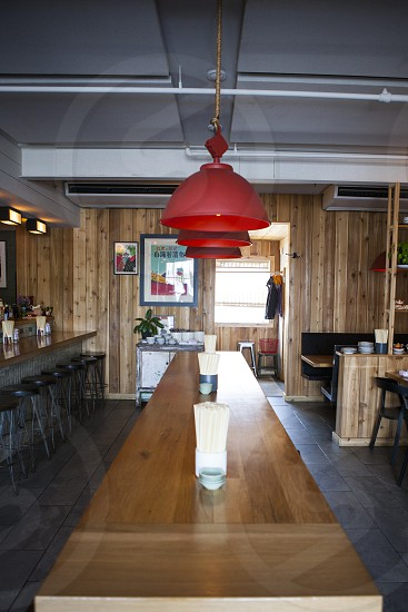 brown wooden rectangular table with white paper towel on top and red pendant lamp restaurant photo