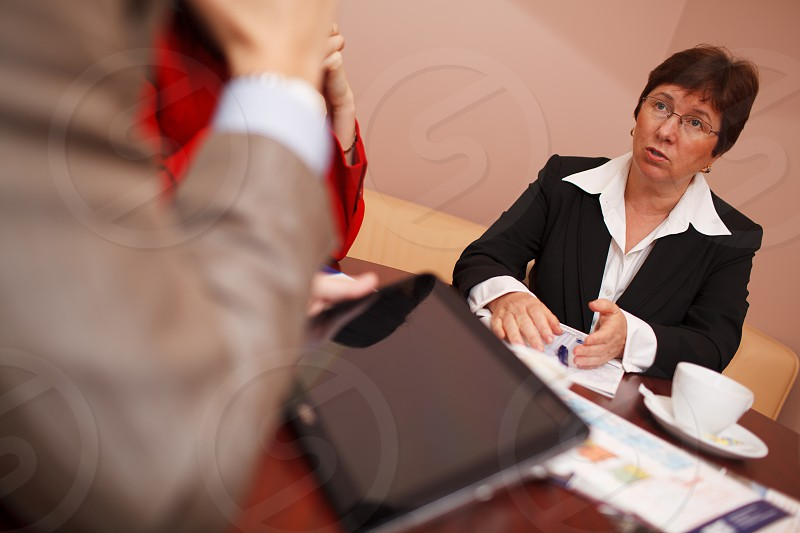 Businesswoman explaining something in a meeting gesturing with her hand as she speaks low angle view past the elbow of a male colleague photo