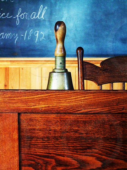 Old school house desk with the bell and chalkboard photo