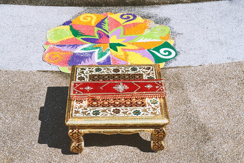 The chantry with red velvet fabric and colorful rangoli art decorated from flour rice sand one of the traditional part of indian wedding ceremony photo