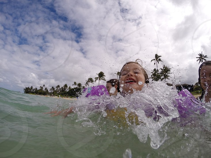 Action shot frozen in time jumping in the ocean kid child splash mid air photo