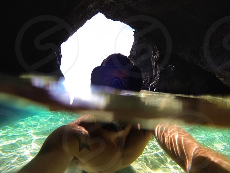 man in sea cave swimming with sea goggles photo