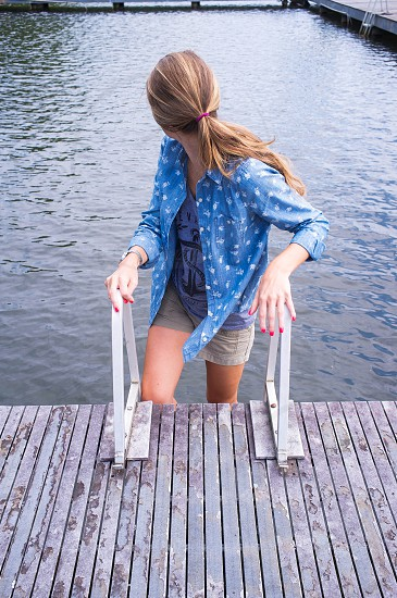 woman in blue button up shirt near swimming pool photo