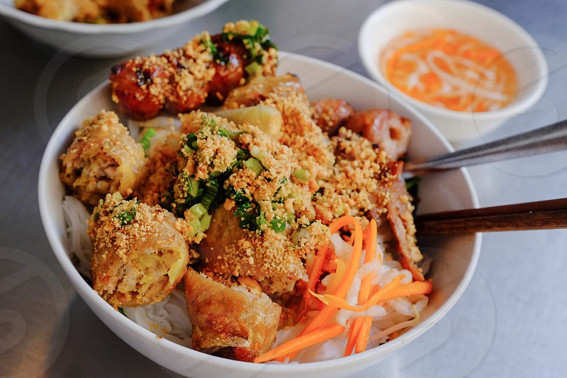 Bún thịt nướng (Vietnamese: rice noodles [with] grilled meat) is a popular Vietnamese dish of cold rice-vermicelli noodle topped with grilled pork fresh herbs like basil and mint fresh salad giá (bean sprouts) and chả giò (spring rolls) photo
