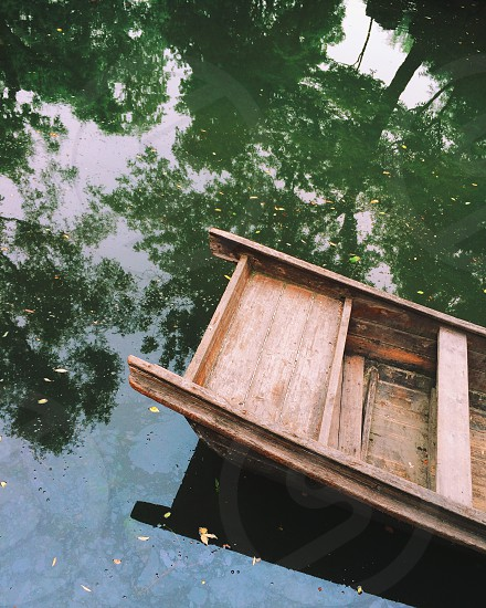 Small Chinese wooden boat with reflected trees in the Humble Administrator's Garden Suzhou China photo